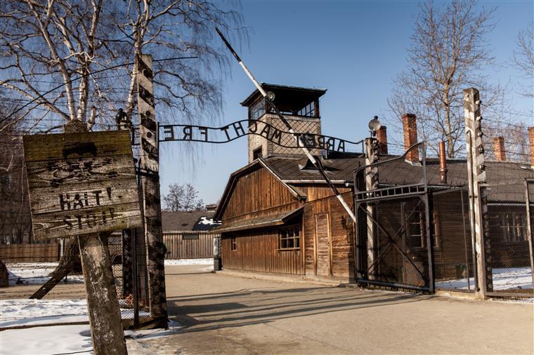 Nus e acorrentados no portão de Auschwitz